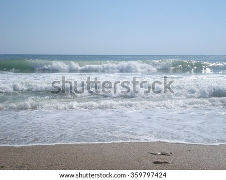 Sparkling foamy waves moving towards beach in sunny summer day - stock photo