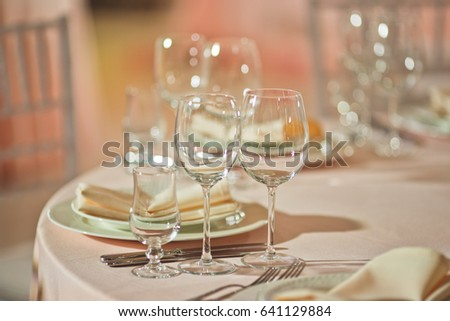Sparkling glasses stand by plate on dinner table