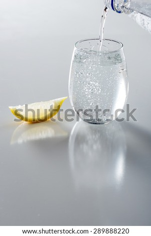 Sparkling water being poured into glass - stock photo