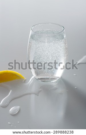 Sparkling water in  glass with lemon, water spilled - stock photo