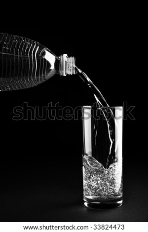 Sparkling water pouring into a glass from plastic bottle - stock photo