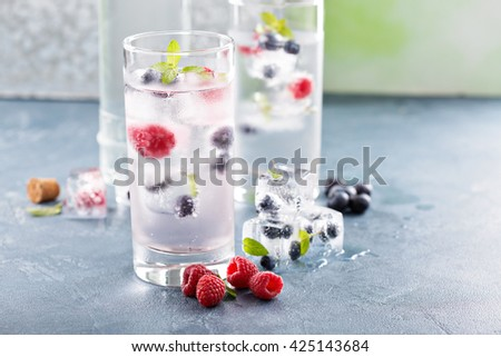 Sparkling water with berry and mint ice cubes - stock photo