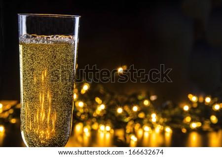 Sparkling Wine and Lights/Evening Celebration/ Glass filled with sparkling wine and lights - stock photo