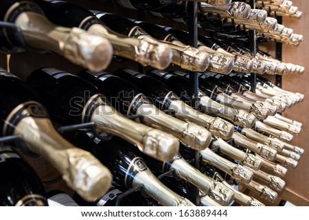 Sparkling Wine Bottles in rack - stock photo