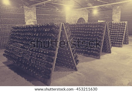 Sparkling wine glass  bottles fermenting  in winery cellar   - stock photo