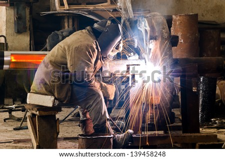 Sparks and drops of molten metal during work of welder. - stock photo
