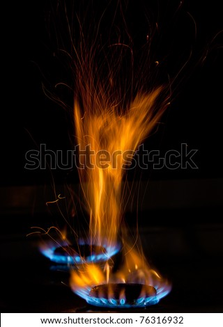 sparks and flames above gas stove burning with blue flames - stock photo