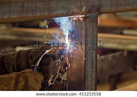 Sparks and jets of smoke when welding of steel structures semi-automatic welding in shielding gases - stock photo