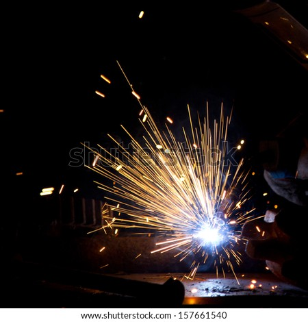 Sparks during metal cutting over black - stock photo