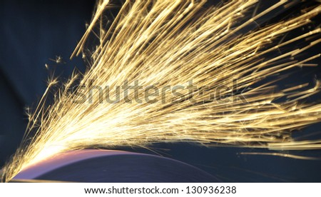 Sparks from a grinding wheel while knife sharpening - stock photo