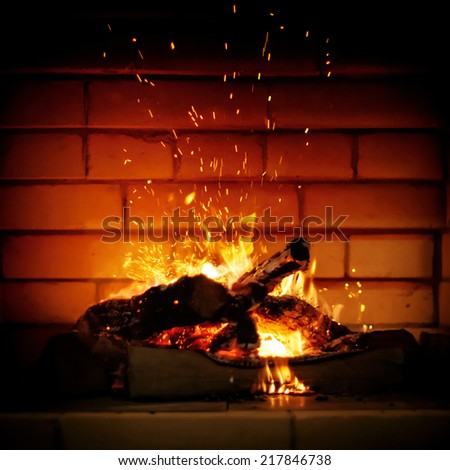 Sparks from Fire in a Fireplace on a brick wall background, square image with vignette effect  - stock photo