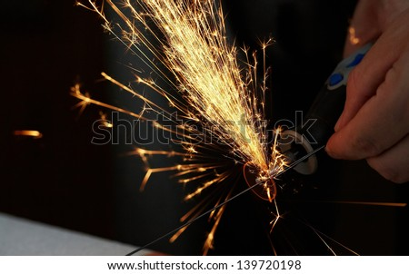 Sparks while sawing metal. close up - stock photo