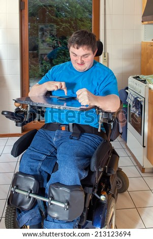Spastic young man confined to a multifunctional wheelchair as a result of infantile cerebral palsy caused by birth complications - stock photo