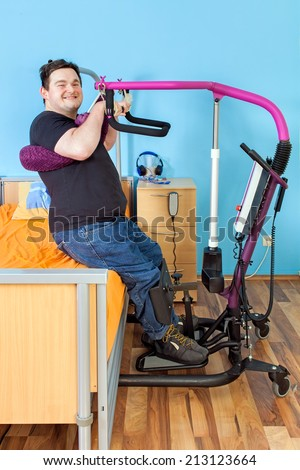Spastic young man with infantile cerebral palsy from birth complications using a patient lift to transfer from a healthcare bed to his wheelchair giving the camera a happy friendly smile - stock photo