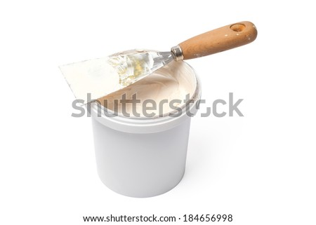 Spatula and bucket with plastering material isolated on white background