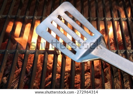 Spatula On The Hot Empty Clean Flaming Grill Close-up. Summer Outdoor Backyard BBQ Party or Cookout or Picnic Concept. - stock photo