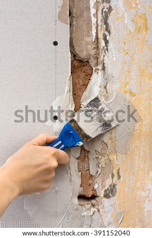 spatula with plaster in hand during repair, closeup - stock photo