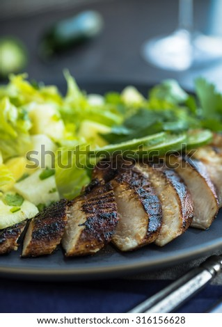 Spciy jerk chicken with lime and green salad with cilantro - stock photo