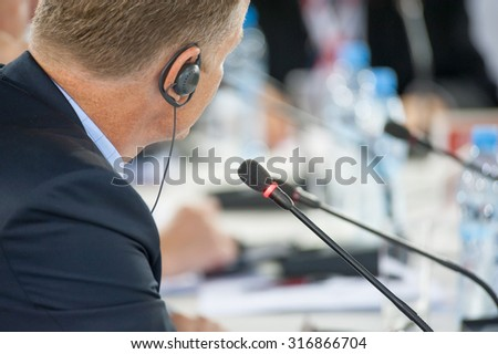 Speaker at business conference and presentation. Focus to microphone. No recognizable faces - stock photo