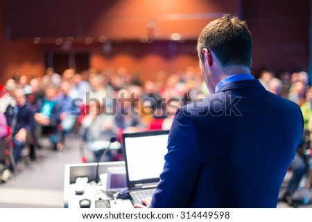 Speaker at Business Conference with Public Presentations. Audience at the conference hall. Entrepreneurship club. Rear view. Horizontal composition. Background blur.