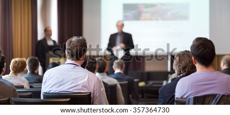 Speaker Giving a Talk at Business Meeting. Audience in the conference hall. Business and Entrepreneurship. Panoramic composition suitable for banners. - stock photo