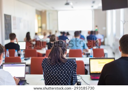 Speaker Giving a Talk at Business Meeting. Rear view of audience in the conference hall. Business and Entrepreneurship. Copy space on white board. - stock photo