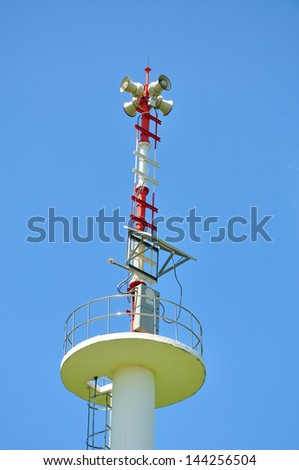 Speaker on high tower and blue sky - stock photo