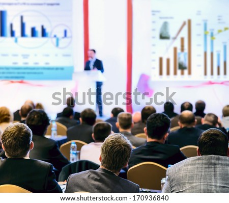 Speaker on the podium. People at conference hall, rear view - stock photo