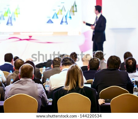 Speaker on the podium. People at the conference hall. Rear view - stock photo