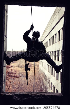 Spec ops police officer SWAT during rope exercises with weapons, silhouette - stock photo