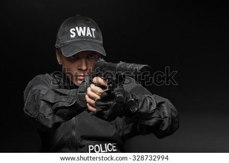Spec ops police officer SWAT in black uniform with pistol studio  - stock photo