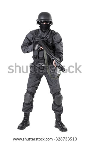 Spec ops police officer SWAT in black uniform with shotgun studio shot - stock photo