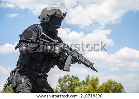 Spec ops soldier in black uniform and face mask with his rifle - stock photo