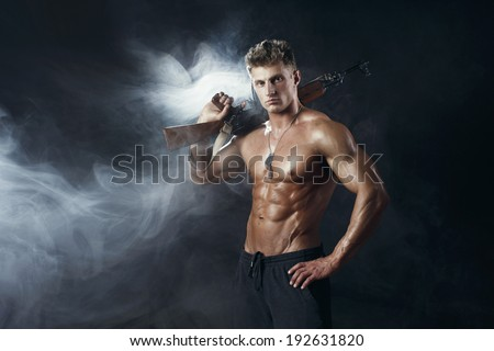 Special force man with the assault rifle gun on dark background with smoke - stock photo
