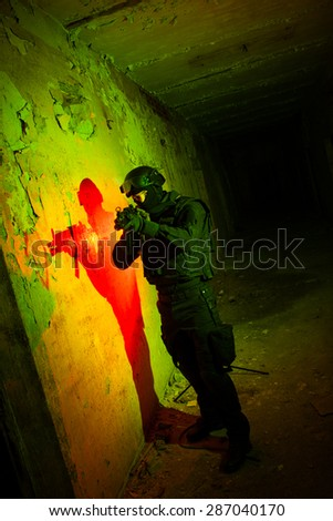 Special forces/ anti-terrorist police unit/private military contractor during night CQB hostage rescue raid/operation/mission (red and green light for underline the atmosphere) - stock photo