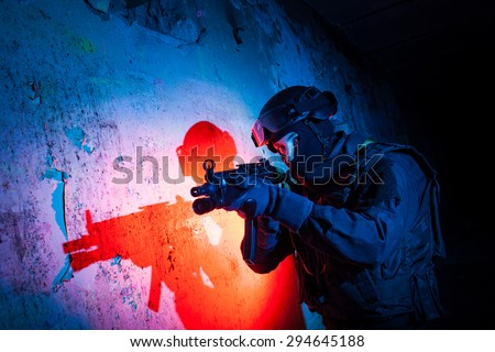 Special forces/ anti-terrorist police unit/private military contractor during night CQB hostage rescue raid/operation/mission (red and blue light for underline the atmosphere) - stock photo