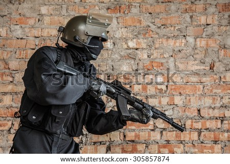Special forces operator in black uniform and bulletproof  - stock photo