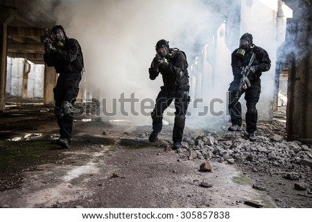 Special forces operator in black uniform in the smoke - stock photo