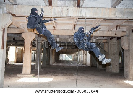Special forces operators during assault rappeling with weapons  - stock photo