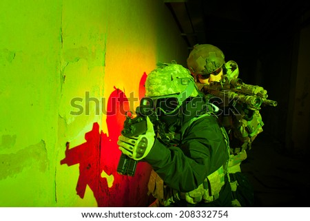 Special forces or contractor team during night mission/operation (red and green light for underline the atmosphere) - stock photo