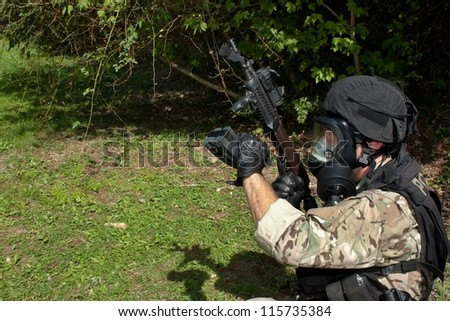 "Special Forces soldier charged gun, assault rifle ""sa.58"",  in a gas mask - stock photo"