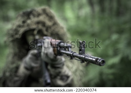 Special forces soldier in heavy camouflage hidden in forest, aiming with assault rifle - focus on barrel - stock photo