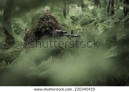 Special forces soldier in heavy camouflage hidden in forest, aiming with assault rifle. Hidden behind trees.  - stock photo