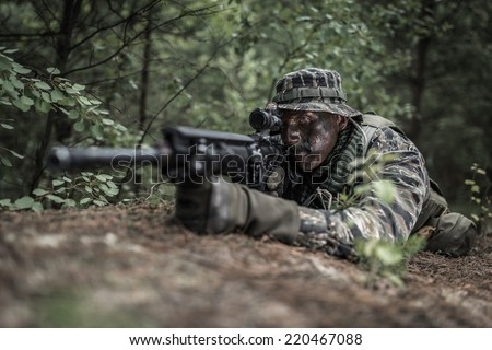 Special forces soldier lying on the ground, preparing to shoot. - stock photo