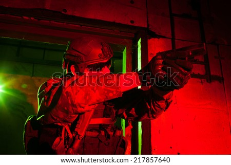 Special forces soldier or contractor during night mission/operation (red and green light for underline the atmoshpere) - stock photo