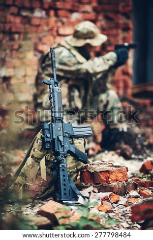 Special forces soldier with rifle in the ruins - stock photo