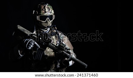Special forces soldier with rifle on dark background - stock photo