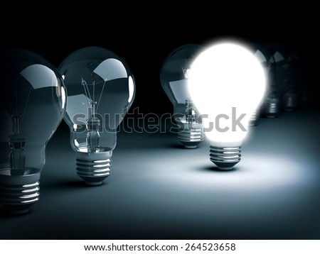 Special idea concept illustrated with a lit light bulb among various unlit ones in a dark sinister ambient