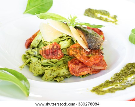 special recipe, rainbow trout and cheese on green pasta serving on white dish