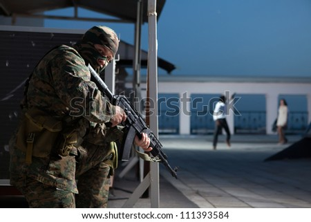Special squad soldier in ambush. Gangsters on the background. - stock photo